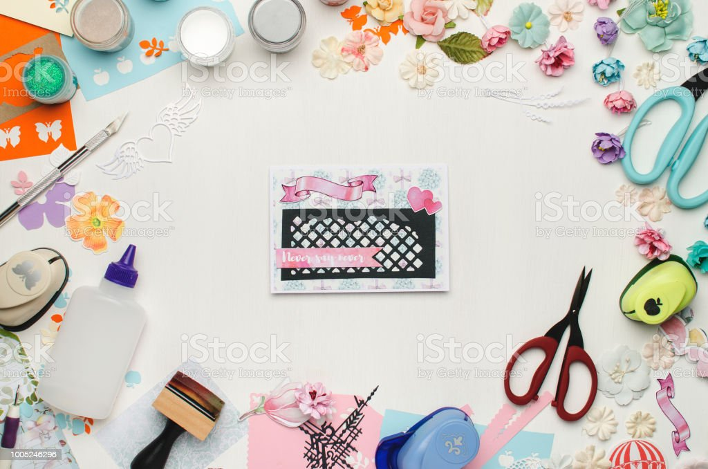 Bright card in the center on a white background surrounded by colored paper, paper flowers and scrapbooking materials Bright card in the center on a white background surrounded by colored paper, paper flowers and scrapbooking materials. Top view Art Stock Photo