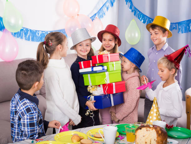 Bright children presenting gifts to girl birthday Bright children presenting gifts to girl during birthday party group of friends giving gifts to the birthday girl stock pictures, royalty-free photos & images