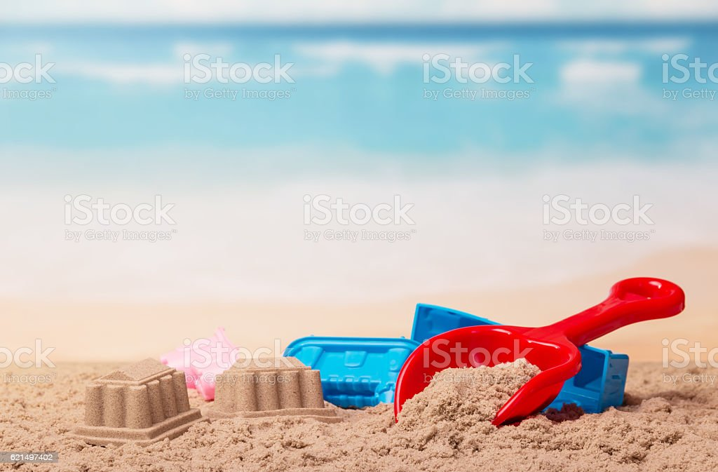 Bright children's toys in the sand against sea. Lizenzfreies stock-foto