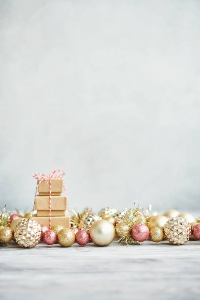 Bright Christmas Background with rose pink and gold decorations with gift stack on white wood stock photo