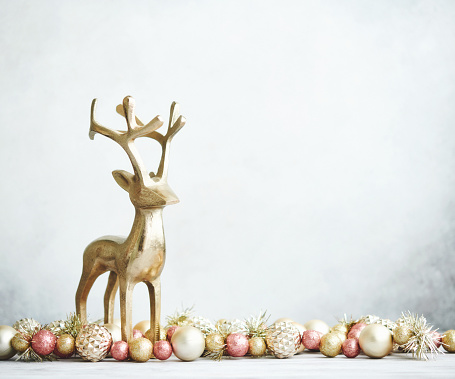 Bright Christmas Background with rose pink and gold decorations with gold reindeer on white wood