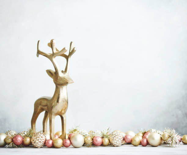 Bright Christmas Background with rose pink and gold decorations with gold reindeer on white wood stock photo
