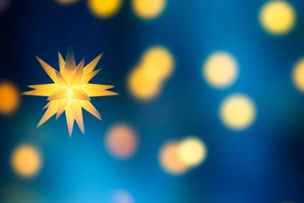 heller weihnachtsstern auf abstraktem glänzendem hintergrund - weihnachtssterne aus papier stock-fotos und bilder