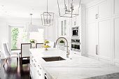 Bright horizontal image of classic white kitchen, with marble island.
