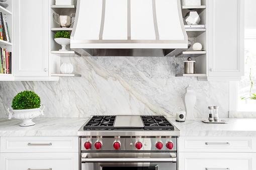 Bright horizontal image of classic white kitchen, with gas range and marble backsplash.