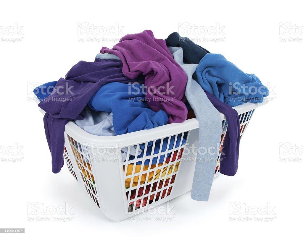 Bright clothes in laundry basket. Blue, indigo, purple. Bright clothes in a laundry basket on white background. Blue, indigo, purple. Basket Stock Photo