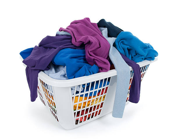 Bright clothes in laundry basket. Blue, indigo, purple. stock photo