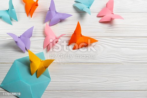 Bright coloful paper butterfiles flying out of the envelope. Greetings card. Overhead flat lay with copy space for your text