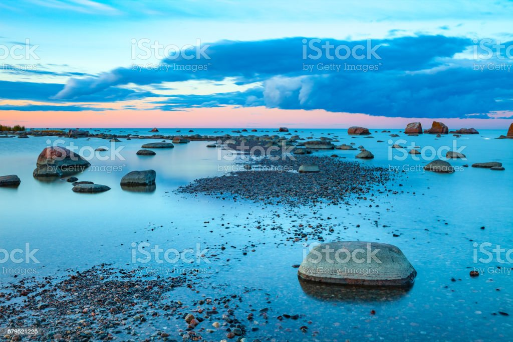 Bright colored sea sunset with stones along the coast and small peninsula royalty-free stock photo
