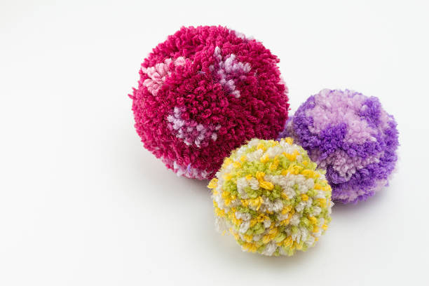 bright colored wool pom poms isolated on white - pompon stockfoto's en -beelden