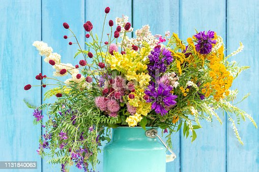 Bright colorful bouquet of wild flowers in starm tin can vase on background blue wooden boards. Template for postcard or your design Concept Women's day or Mothers Day, Hello summer Hello spring.