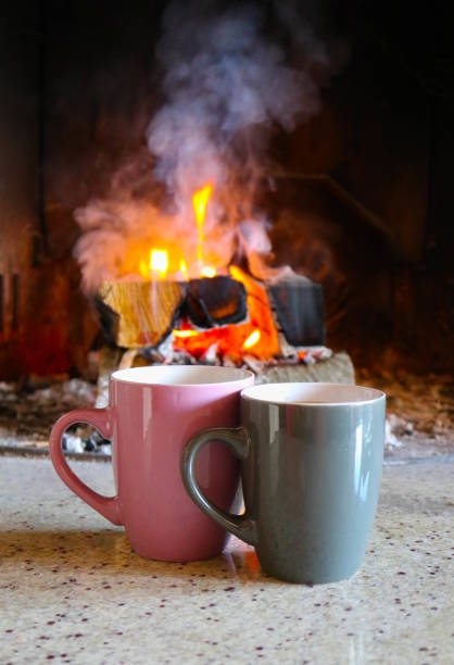 Bright colorful flame, burning wood at the fireplace, two coffee caps. stock photo