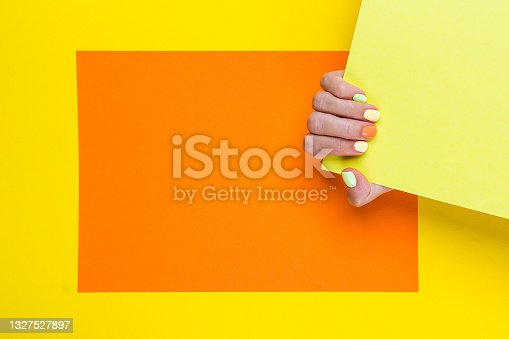 istock Bright colorful gel manicure on yellow and orange background. 1327527897