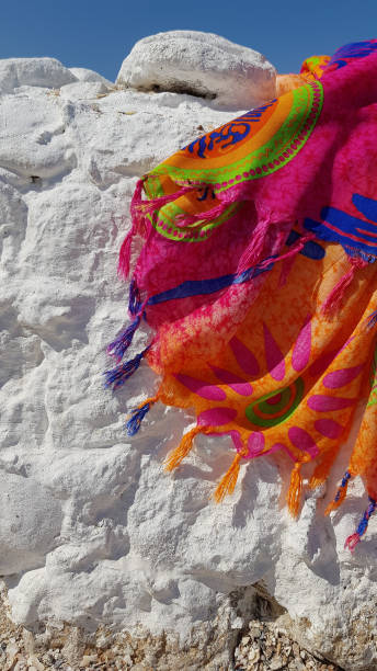 Bright colorful pareo with blue and orange color tassels on rough white stone background of beach and blue sky. Vacation concept with tropical pattern textile scarf waving in wind. stock photo