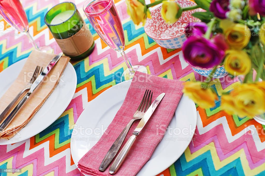 Bright colorful table setting with chevron tablecoth stock photo