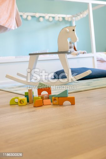 istock Bright colorful wooden blocks toy and a wooden horse swing in a beautiful baby room 1186300326