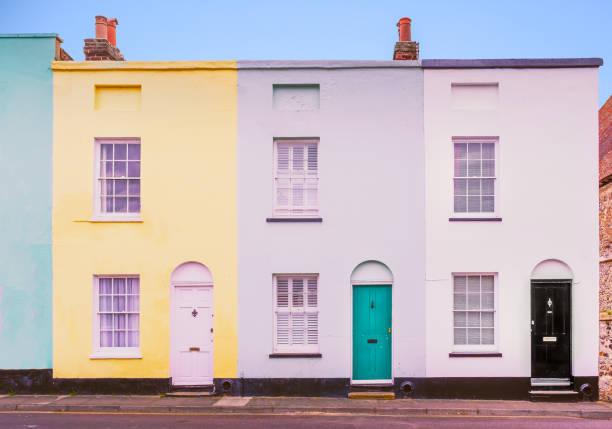Leuchtend bunte symmetrische Reihe, Terrasse Häuser mit jeweils zwei Schiebefenstern und Lünette Bogen über den Türen, die auch Türklopfer. – Foto