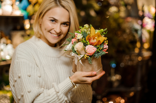 bright composition of flowers and fir branches in box in the hands of woman.