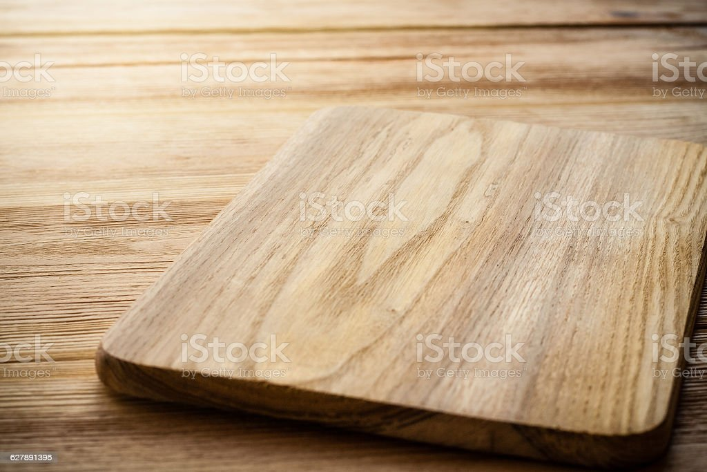 Bright cutting board on a background of the wooden table stock photo