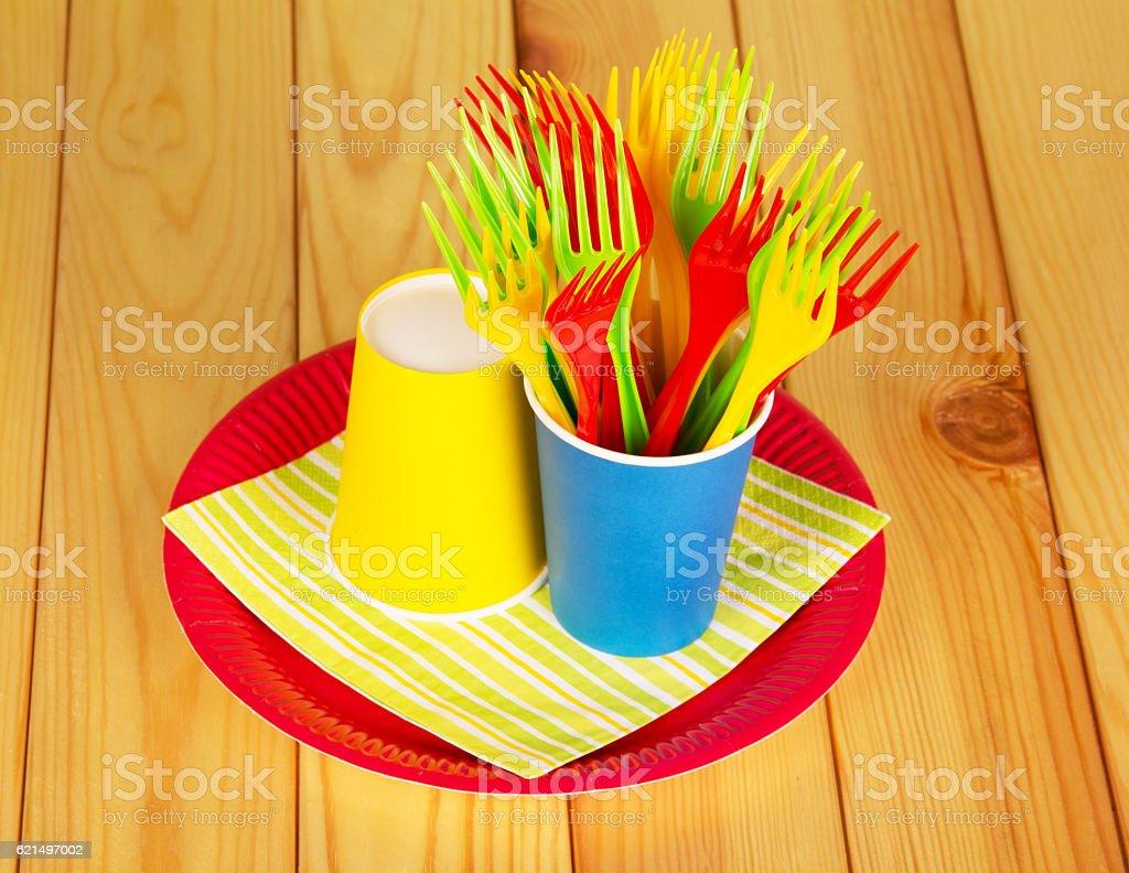 Bright disposable paper cups, plastic forks, plate on alight wood. photo libre de droits