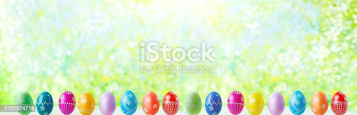 912300146 istock photo bright early colored easter eggs on a sunny spring background 1127574718