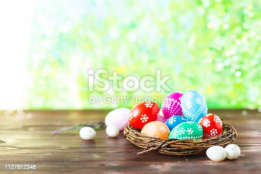 912300146 istock photo bright early colored easter eggs on a sunny spring background 1127612348