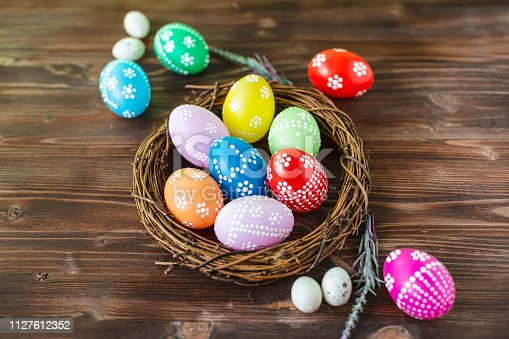 912300146 istock photo bright early colored easter eggs wooden background 1127612352