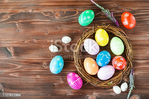 912300146 istock photo bright early colored easter eggs wooden background 1127612354