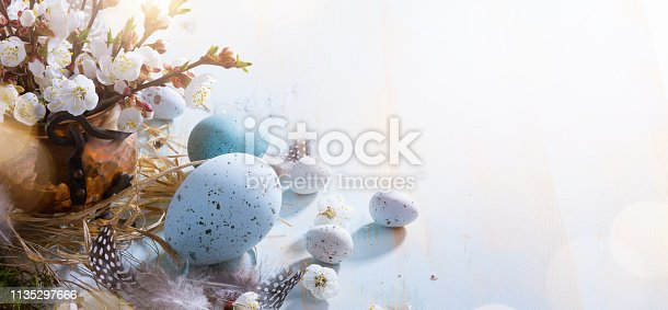 istock bright Easter background;  Easter eggs basket and sprig flowers on blue table background 1135297666