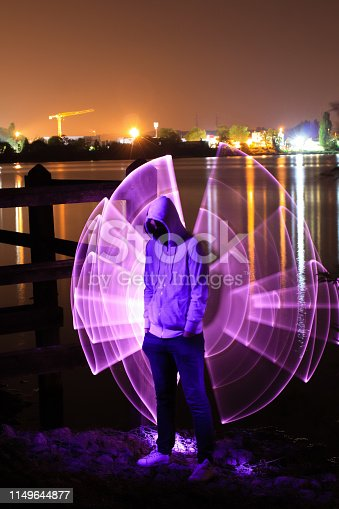 Man standing in front of a lake with wings drawn in lightpainting