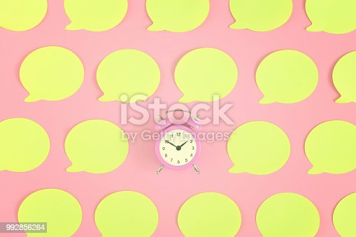istock Bright, empty yellow stickers on a pink background. In the center is a small pink alarm clock. 992856264