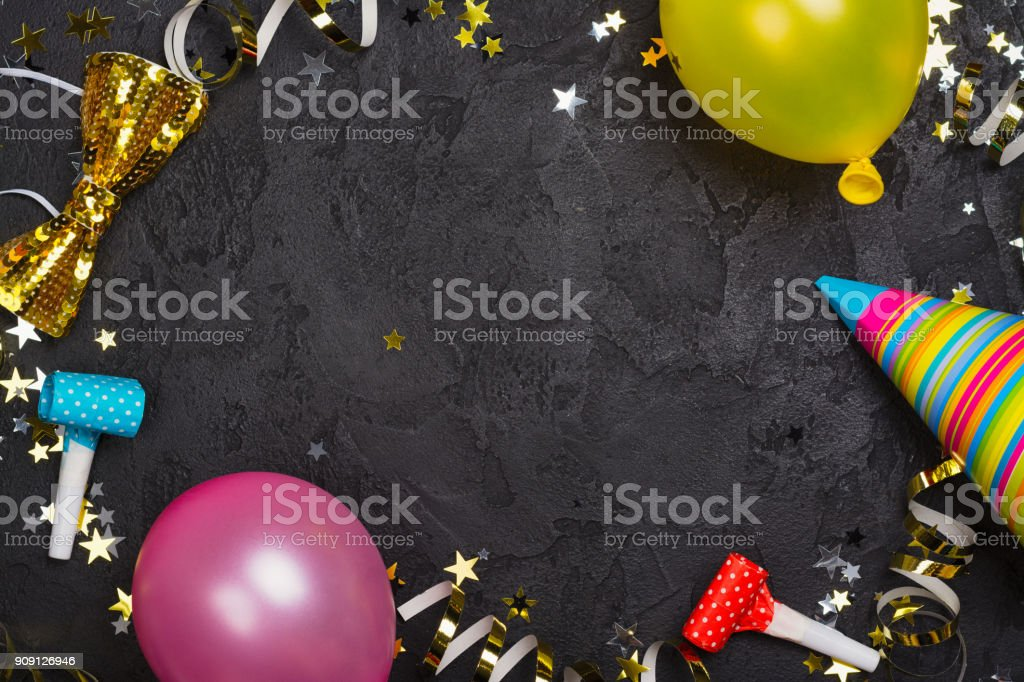 Bright festive carnival background with hats, streamers, confetti and balloons stock photo