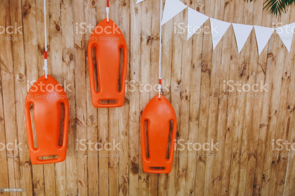 Bright festive decorations for children's happy birthday party in the nautical theme in the form of orange boats and white garlands of triangles on the background of wooden wall. Organization events stock photo