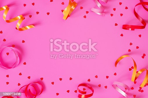 1093222958 istock photo Bright festive pink background with streamers and hearts confetti 1093223438