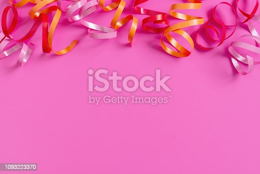 1093222958 istock photo Bright festive pink background with streamers 1093223370