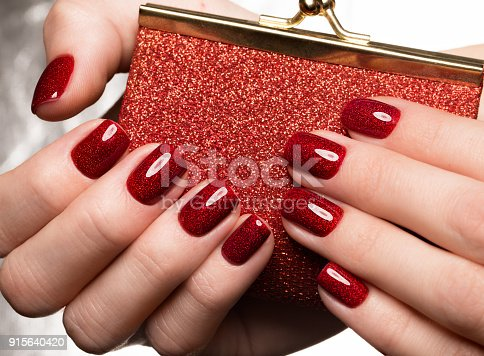 istock Bright festive red manicure on female hands. Nails design 915640420