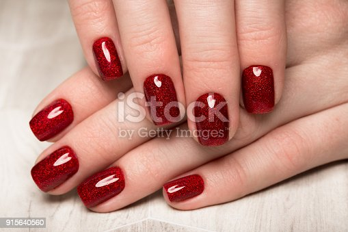 istock Bright festive red manicure on female hands. Nails design 915640560