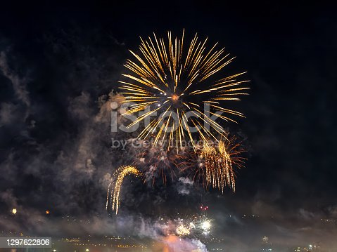 Bright fireworks sparkle in the dark sky. The small town celebrates with colorful fireworks at night. Fireworks smoke cloud in the sky. Outdoor night scene. Festive mood and holidays. Real life.