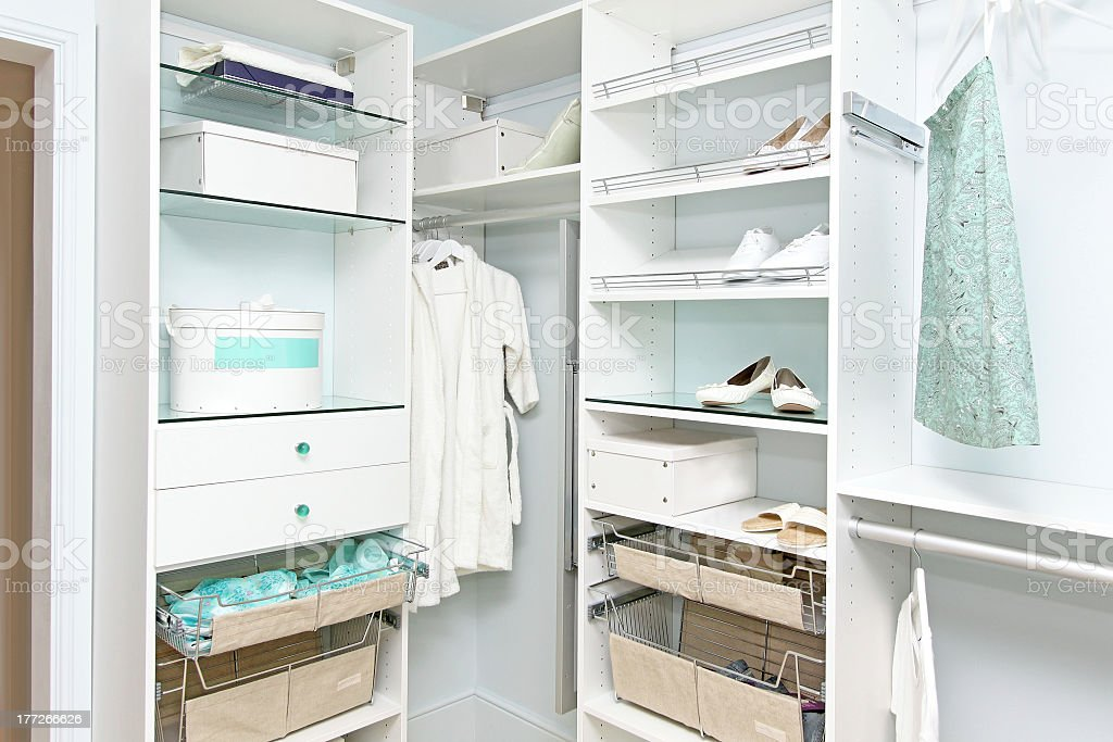 A bright fitted wardrobe with white shoes and clothes stock photo