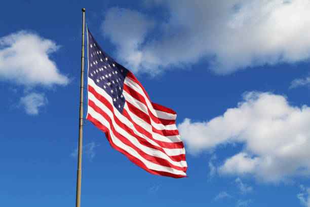 bright flowing waving american flag sunny day white clouds stock photo