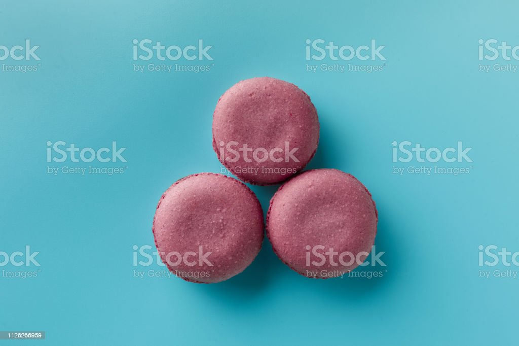 Bright food photography of macrons on blue background. Copy space. maroon. Top view stock photo