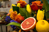Bright fruit spring bouquet of yellow tulips,blue hyacinths,speedwell,red ranunculus,orange roses,grapefruit and lemon.Present concept for Birthday, mother's Day, 8 March.Selective focus