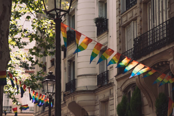 Bright garlands of striped triangle banners in colors of LGBTQ flag on street of Paris France stock photo