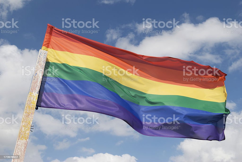Bright Gay Pride Rainbow Flag Blue Sky Clouds royalty-free stock photo