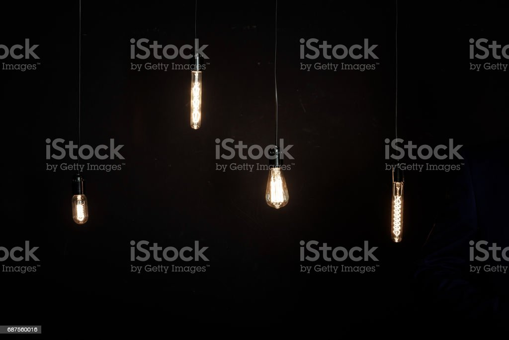 Bright glowing light bulbs of different shapes on dark background stock photo