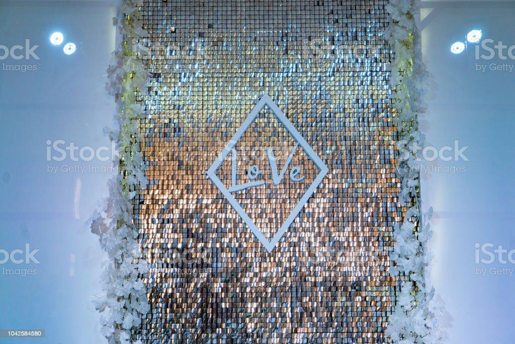ljusa golden vägg med inskriften av ordet kärlek är dekorerad med vita program på sidorna på bröllopet i restaurangen bildbanksfoto