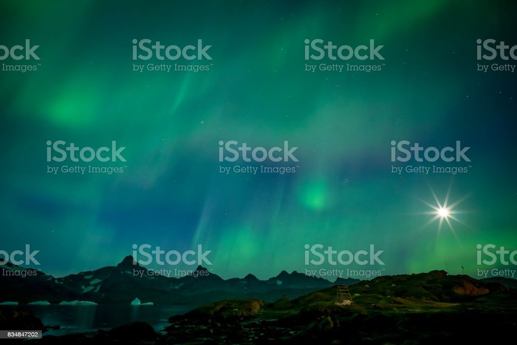 Bright green Aurora with starburst moon stock photo