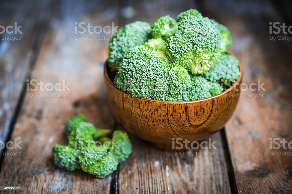 Bright green broccoli in a wooden bowl on a wooden table stock photo