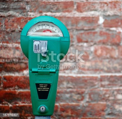 Green parking meter with old brick wall in the background out of focus.All manufacture ID has been removed