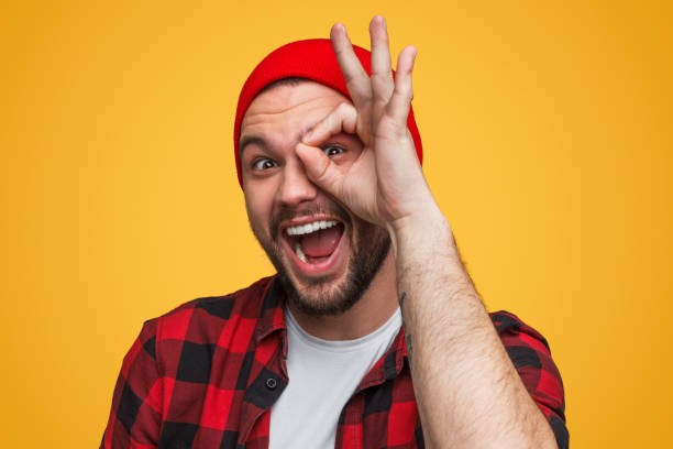 Bright guy looking through fingers at camera Cheerful excited hipster making OK gesture and looking through hand at camera on bright orange background grimacing stock pictures, royalty-free photos & images